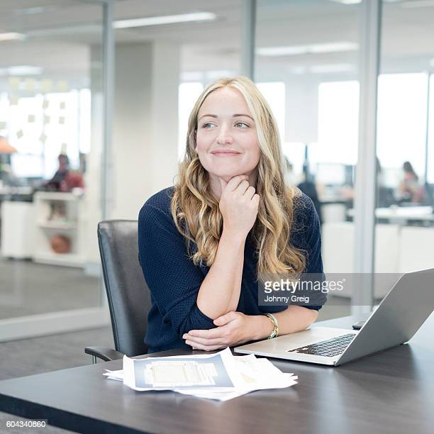Portrait of businesswoman at desk with laptop, smiling
