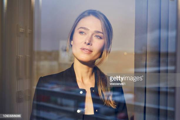 portrait of businesswoman behind windowpane - spiegelung stock-fotos und bilder