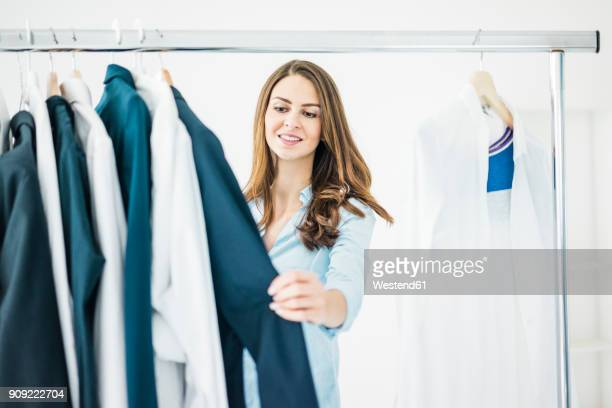 portrait of businesswoman choosing clothes - businesswear stock pictures, royalty-free photos & images
