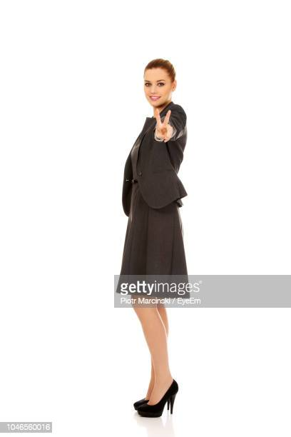 Portrait Of Businesswoman Gesturing Peace Sign Against White Background