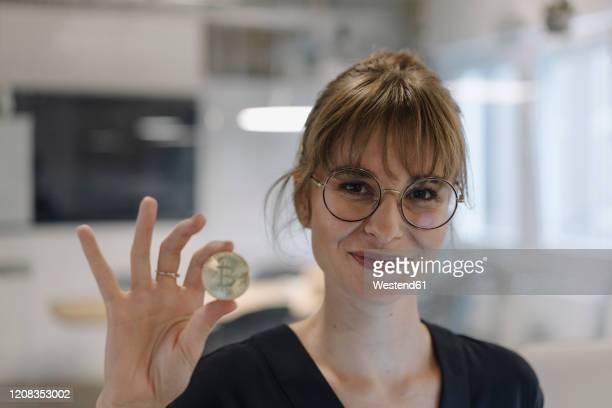 portrait of businesswoman holding bitcoin in office - bitcoin stock-fotos und bilder