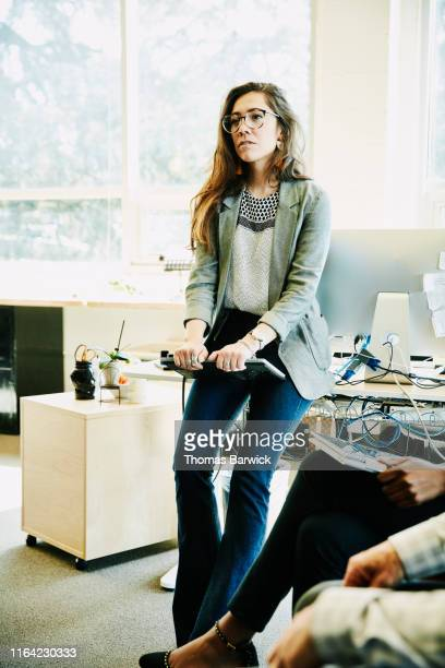 Portrait of businesswoman holding laptop and listening to coworkers during informal meeting in office