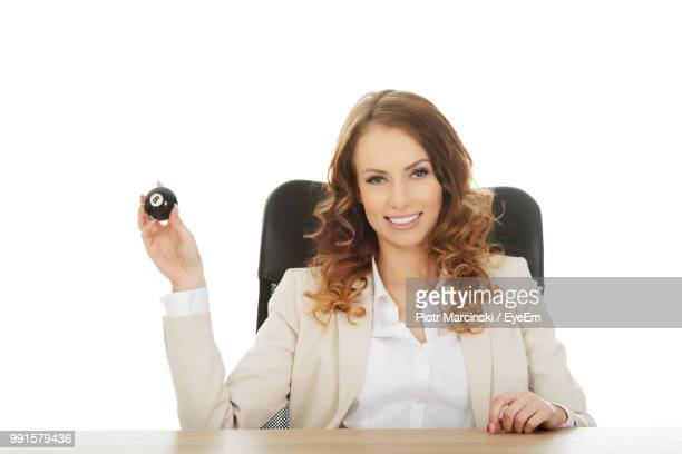 Portrait Of Businesswoman Holding Pool Ball While Sitting On Chair Against White Background