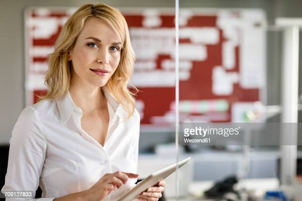 Portrait of businesswoman holding tablet in office