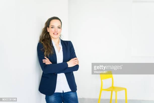 portrait of businesswoman in a room with yellow chair - anzugjacke stock-fotos und bilder