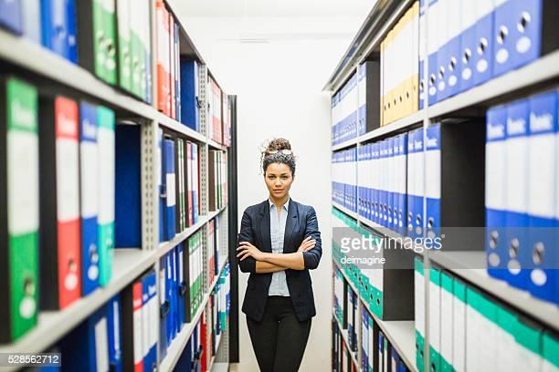 Portrait of businesswoman in basement paper archive