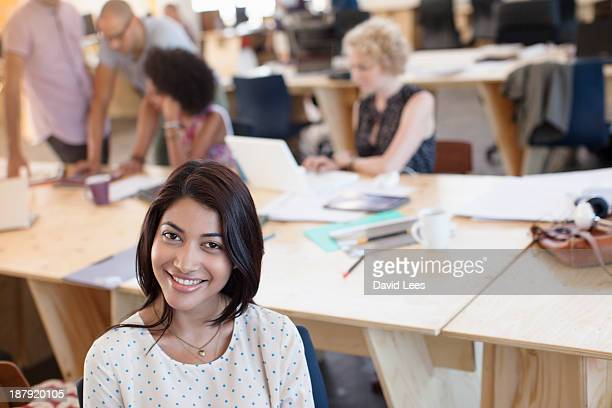 Portrait of businesswoman in busy modern office