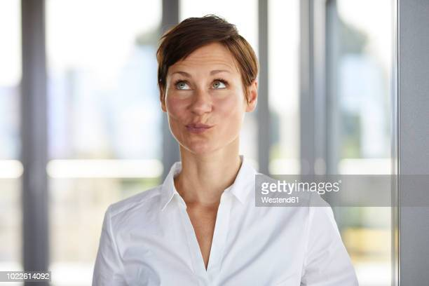 portrait of businesswoman in office pouting looking up - zufriedenheit stock-fotos und bilder