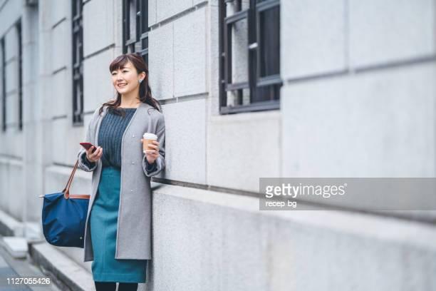 retrato de mulher na rua, mantendo o café de negócios - adulto de idade mediana - fotografias e filmes do acervo
