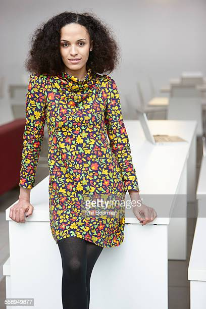 portrait of businesswoman leaning against office desk - floral pattern dress stock pictures, royalty-free photos & images