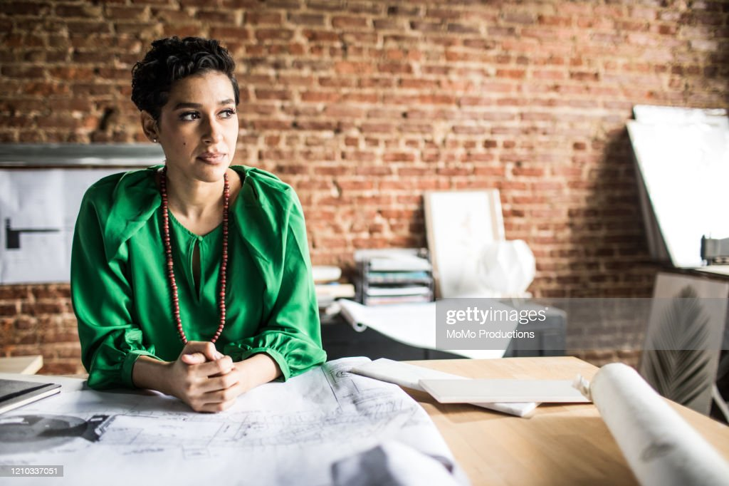 Portrait of Businesswoman looking over architecture blueprints in office : Stockfoto