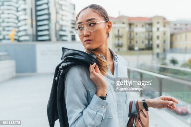 portrait of businesswoman outdoors, carrying leather jacket over shoulder, looking away, pensive expression - looking over shoulder stock pictures, royalty-free photos & images