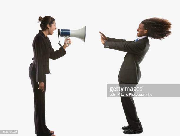 Portrait of businesswoman screaming into megaphone at man