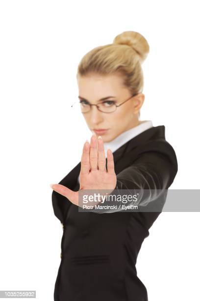 Portrait Of Businesswoman Showing Stop Gesture Over White Background