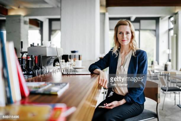 portrait of businesswoman sitting at restaurant bar - bürokleidung stock-fotos und bilder