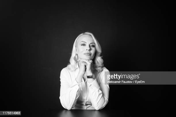 portrait of businesswoman sitting by table against wall - hand on chin stock pictures, royalty-free photos & images