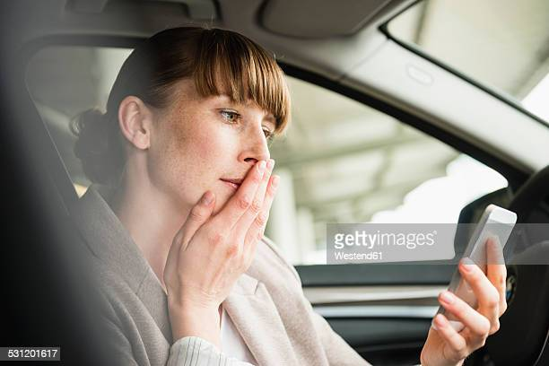 Portrait of businesswoman sitting in a car looking at her smartphone with hand on her mouth