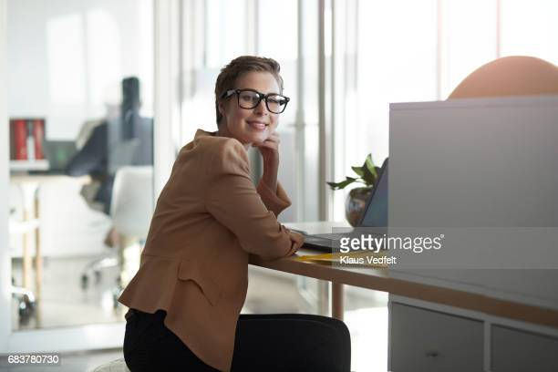 Portrait of businesswoman sitting on fitness ball, at office desk