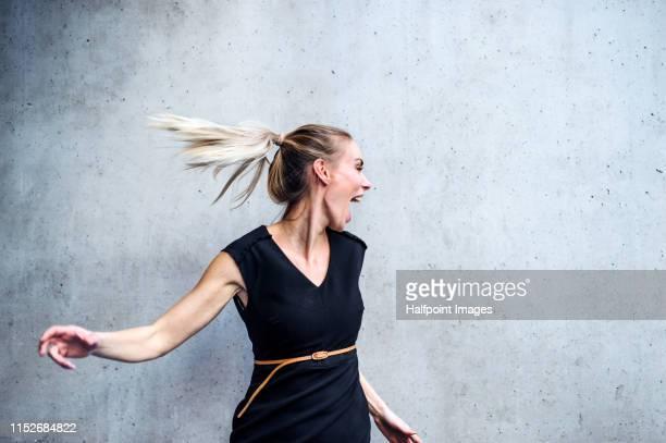 a portrait of businesswoman standing against gray concrete background, having fun. - tourner photos et images de collection