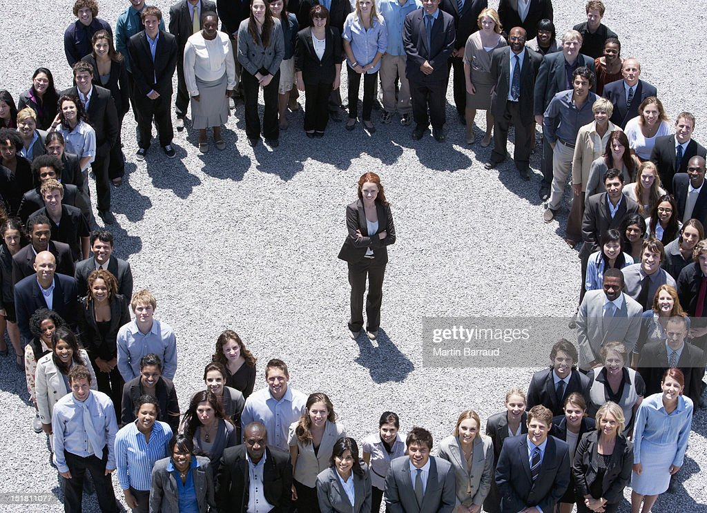 Portrait of businesswoman standing at center of circle formed by business people : Stock Photo