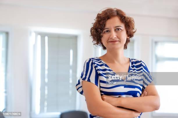 verticale de femme d'affaires restant dans son bureau avec des bras croisés - directrice photos et images de collection