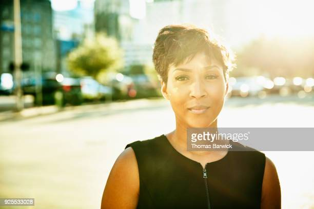 Portrait of businesswoman standing on city sidewalk during early morning commute