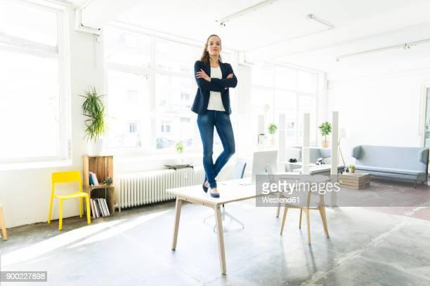 portrait of businesswoman standing on table in a loft - dominanz stock-fotos und bilder