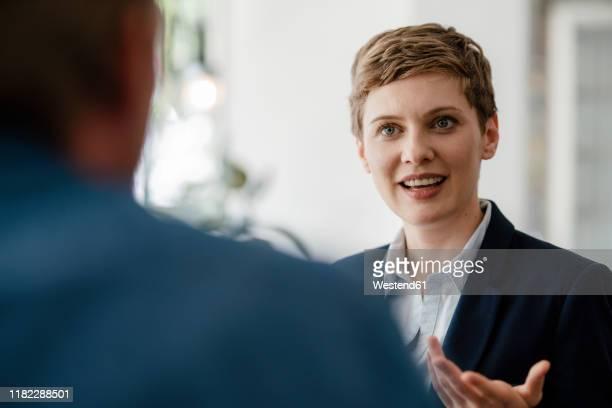 portrait of businesswoman talking to a colleague - discussion stock-fotos und bilder