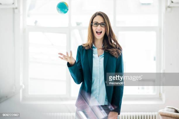 portrait of businesswoman throwing small globe in the air - arremessar - fotografias e filmes do acervo