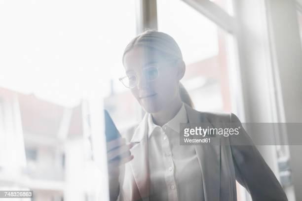 portrait of businesswoman using cell phone - hell beleuchtet stock-fotos und bilder