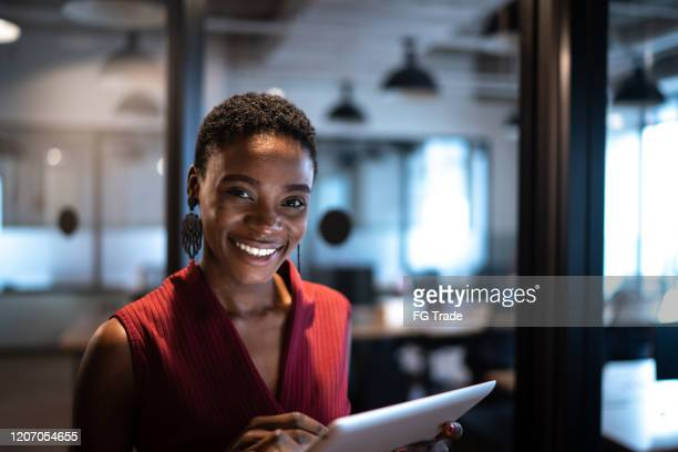 portrait of businesswoman using digital tablet at office - black stock pictures, royalty-free photos & images