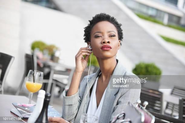 portrait of businesswoman using earphones outdoors - cheveux noirs photos et images de collection