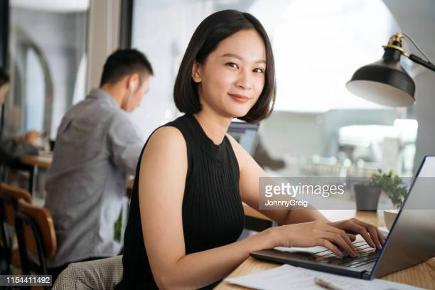 portrait of businesswoman using laptop and smiling towards camera - mid adult women stock pictures, royalty-free photos & images