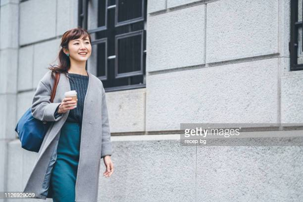 portrait of businesswoman walking in street while holding coffee - coat stock pictures, royalty-free photos & images