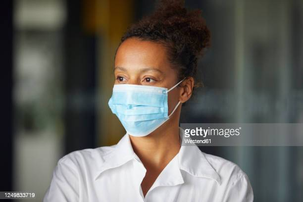 portrait of businesswoman wearing light blue protective mask looking at distance - black blouse stock pictures, royalty-free photos & images