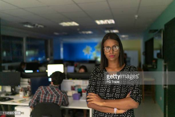 portrait of businesswoman with arms crossed in the office at night - incidental people stock pictures, royalty-free photos & images