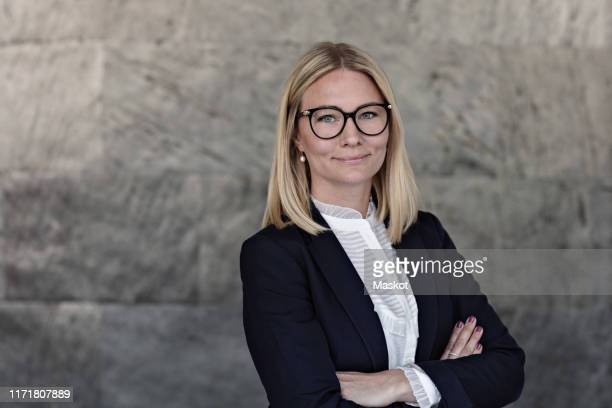 portrait of businesswoman with arms crossed standing against wall in office - 35 39 jahre stock-fotos und bilder