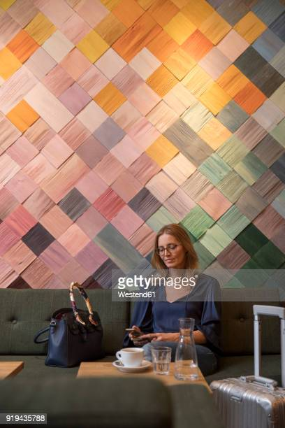 portrait of businesswoman with baggage in a cafe looking at cell phone - multi coloured purse stock photos and pictures