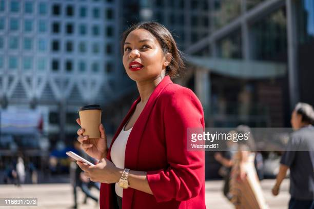 portrait of businesswoman with coffee to go and cell phone, london, uk - black blazer stock pictures, royalty-free photos & images