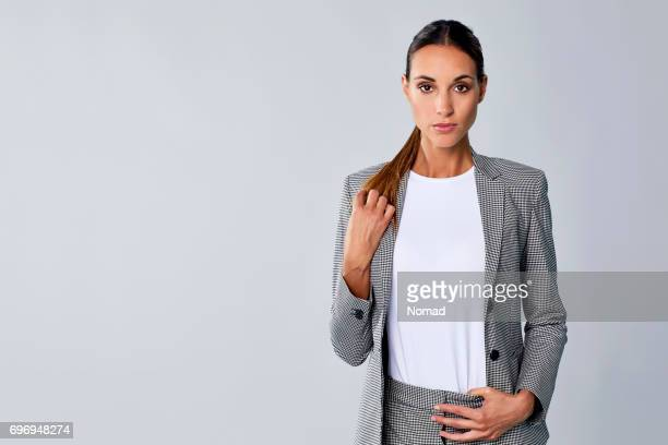portrait of businesswoman with hand in ponytail - ponytail stock pictures, royalty-free photos & images