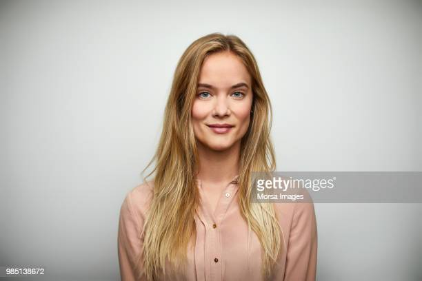 portrait of businesswoman with long blond hair - glimlachen stockfoto's en -beelden