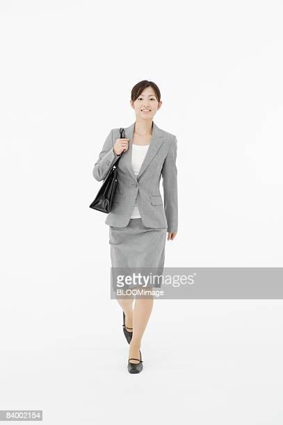 Portrait of businesswoman with shoulder bag, studio shot