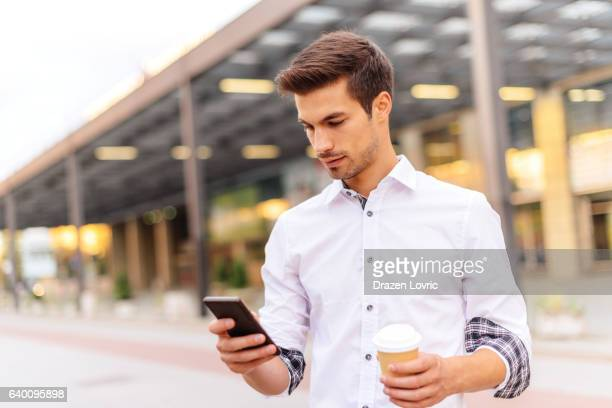 portrait of busy young man with smartphone on street - drazen stock pictures, royalty-free photos & images