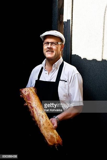 Portrait of butcher holding smoked meat