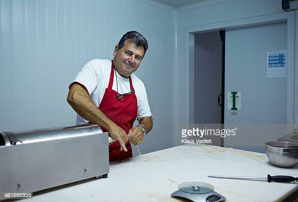 portrait of butcher making sausages - klaus vedfelt mallorca stock pictures, royalty-free photos & images