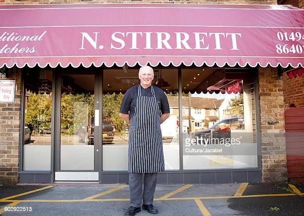 portrait of butcher outside butchers shop - エプロン ストックフォトと画像