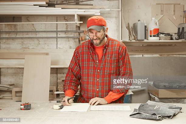 Portrait of cabinet maker checking blueprint at workshop bench