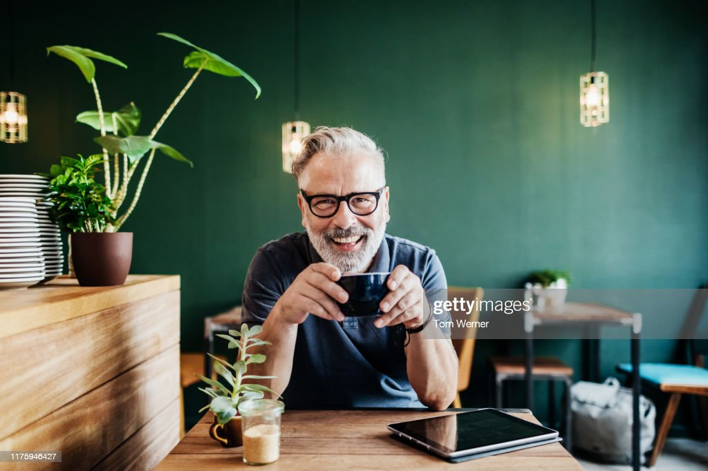 Portrait Of Cafe Customer Smiling While Drinking Coffee : Stock-Foto