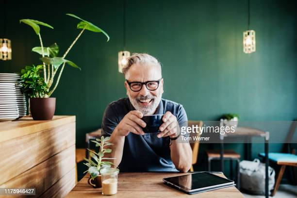 portrait of cafe customer smiling while drinking coffee - oudere mannen stockfoto's en -beelden