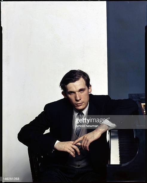 Portrait of Canadian classical pianist Glenn Gould as he poses next to his piano, New York, New York, October 10, 1959.